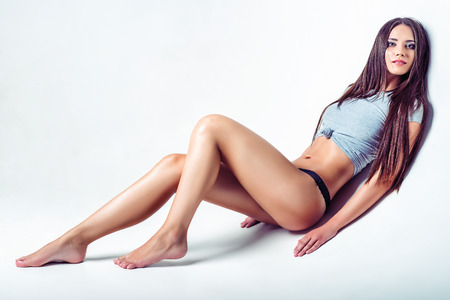 lying on stomach: Studio fashion shot of a beautiful young woman in shirt and panties Stock Photo