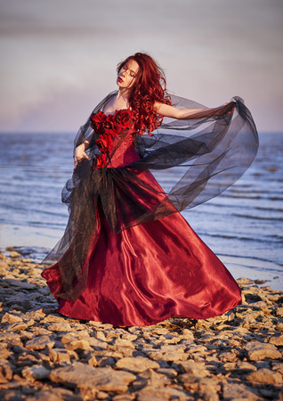red dress: Beautiful young woman in red dress standing on the sea coast