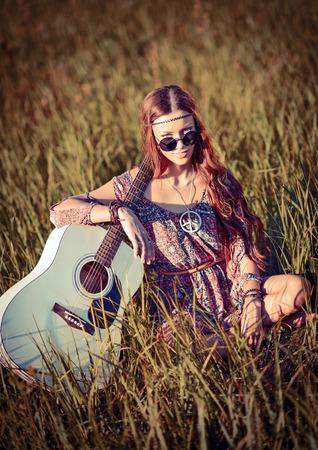 mujer hippie: Chica hippie joven encantadora con la guitarra sentado en la hierba