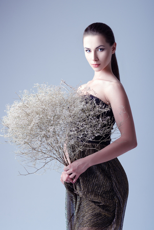 fashion and beauty: Studio fashion shot: a beautiful young woman in dress holding a bouquet of withered flowers