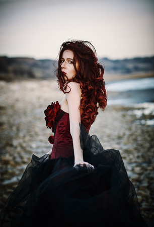 woman red dress: Beautiful sad goth girl standing on the sea shore. Rear view