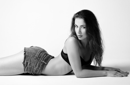 sexy shorts: Fashion shot: a beautiful young girl lying on a floor. Black and white