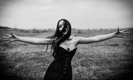 Crying sad goth girl in the autumnal field. Black and white photo