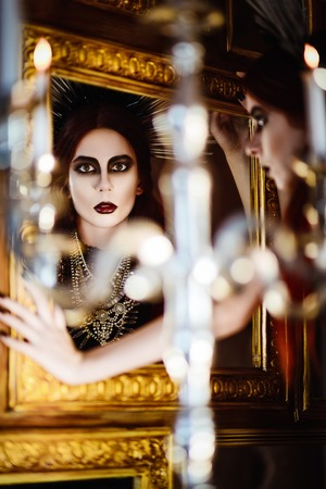 insane insanity: Gothic fashion: mysterious beautiful young woman looking into the mirror