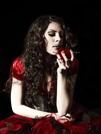 sewn: Horror shot: the strange scary girl with mouth sewn shut tries to eat an apple studded with nails Stock Photo