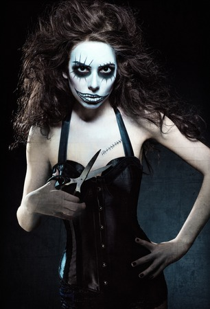 freaks: Young woman in the image of a evil gothic freak clown with scissors in hand. Grunge texture effect Stock Photo
