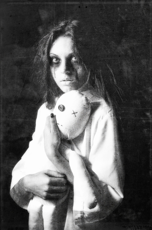 Horror style shot: the mysterious ghost girl with moppet doll in hands. Grunge texture effect Stock Photo