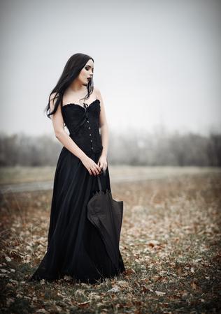 beautiful sad: A beautiful sad goth girl holds black umbrella