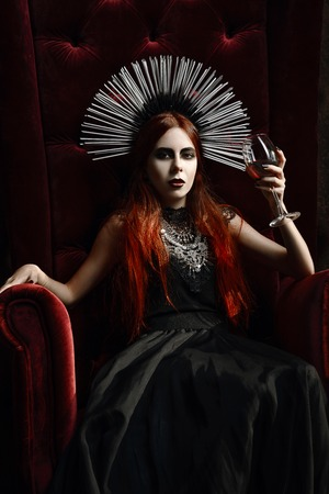 scary halloween: Gothic fashion: young woman sitting in chair and holding a glass of wine