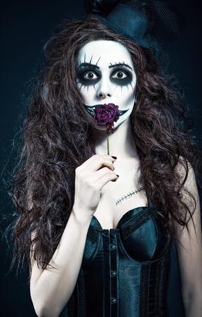payaso: Mujer joven en la imagen de un payaso loco gótico triste sostiene flor marchita