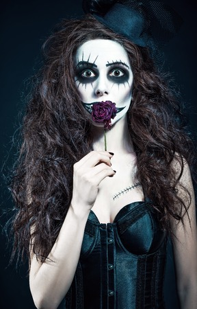 Young woman in the image of a sad gothic freak clown holds withered flower Stock Photo