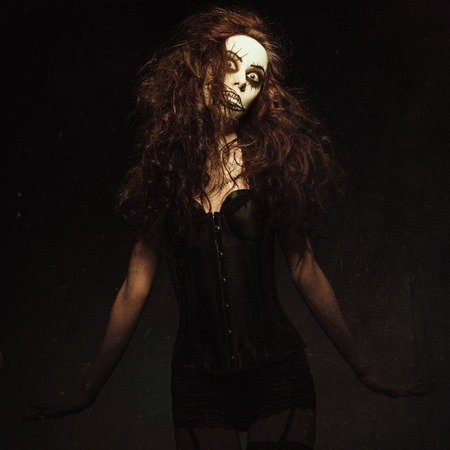 Young woman in the image of a sad gothic freak clown. Grunge texture effect