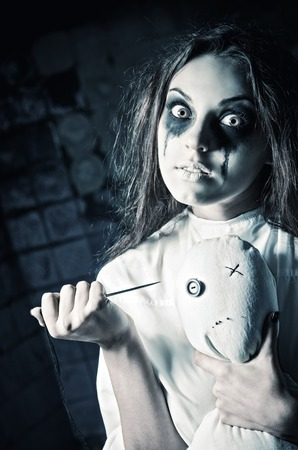Horror style shot: a scary crazy girl with moppet doll and needle in hands. Cold toned