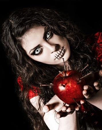 black girl: Horror Schuss: Der merkw�rdige furchtsame M�dchen mit Mund zugen�ht h�lt Apfel mit N�geln beschlagen Lizenzfreie Bilder