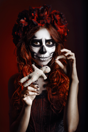mexican girl: Young woman with muertos makeup (sugar skull) piercing a voodoo doll Stock Photo