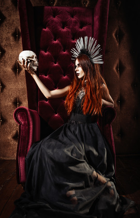 Horror photo: a beautiful goth girl in black dress holds the skull
