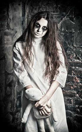 evil girl: Horror scene: the strange mysterious girl with moppet doll in hands