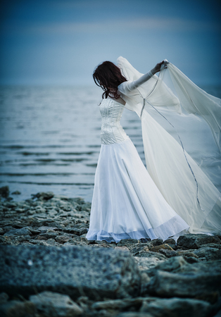 beautiful sad: Beautiful sad girl in white dress standing on the sea shore Stock Photo
