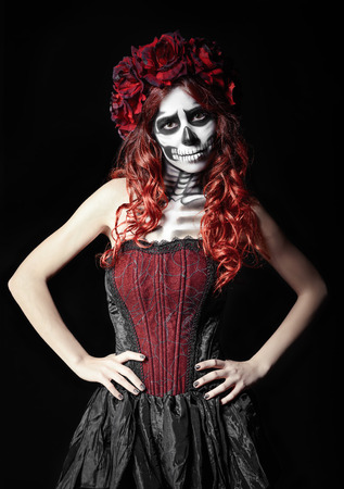 girl in red dress: The sad young woman with calavera makeup (sugar skull) Stock Photo