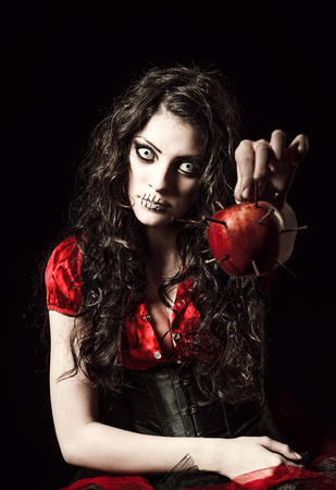 evil girl: Horror shot: the strange scary girl with mouth sewn shut holds apple studded with nails Stock Photo