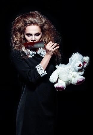 cuchillo: disparo de terror: una chica monstruo de miedo con el juguete del conejo desgarrado y un cuchillo con sangre en las manos