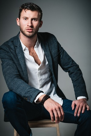 Studio fashion shot: portrait of a handsome young man in jeans, shirt and jacket sitting on bench