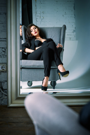 seductive look: Portrait of a beautiful young woman sitting on chair and looking into the mirror