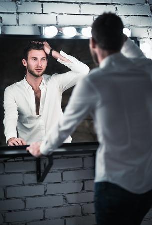 modelos hombres: Retrato de hombre joven y guapo en vaqueros y camisa mirando en el espejo