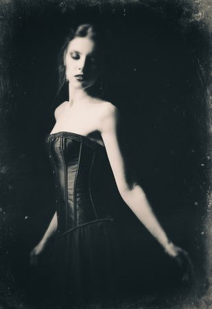 sad old woman: Dramatic retro portrait of a beautiful sad gothic girl among the dark. Old film effect, black and white