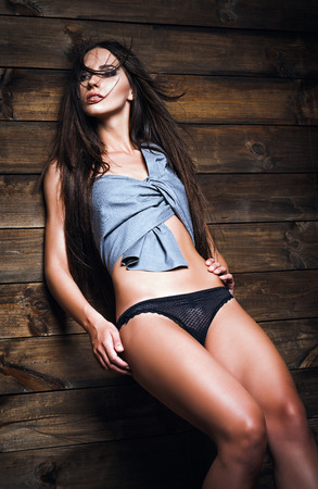 woman panties: Fashion shot: attractive young woman in panties and shirt stands at the wood wall