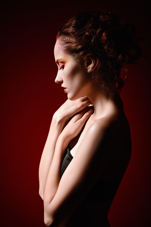 girl posing: Portrait of a beautiful sad redhead girl. Profile view Stock Photo