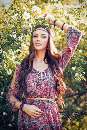 60s hippie: Portrait of a beautiful young hippie girl among the flowers