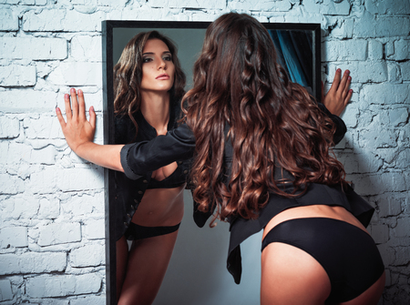 Portrait of a beautiful sexy young woman looking into mirror. Rear view