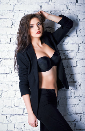 black bra: Studio fashion shot: a beautiful young woman in pants and jacket stands at the wall