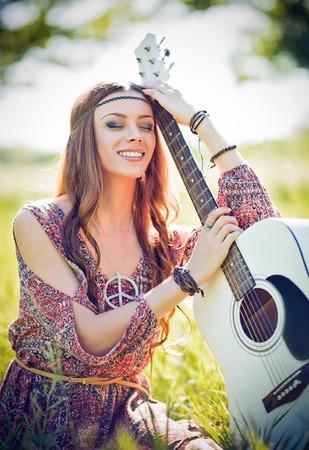 niñas sonriendo: Retrato de una bella mujer sonriendo hippie con la guitarra. tiro al aire libre