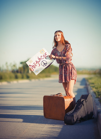 Portrait of a beautiful young hippie woman hitchhiking on the road Stock Photo