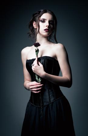 枯れた花を手で保持して美しいゴス少女の肖像画