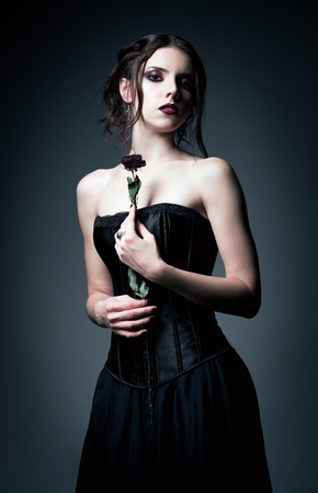beautiful girl face: Portrait of beautiful goth girl holding a withered flower in hands Stock Photo