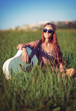 woman guitar: Portrait of a beautiful smiling hippie woman with guitar in the field