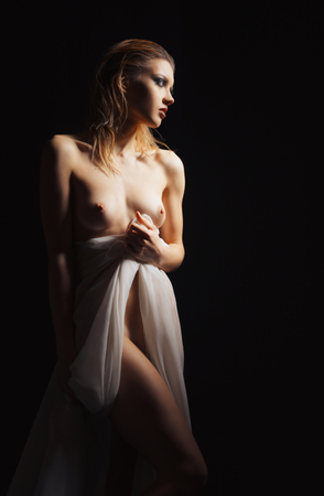 young woman nude: Dramatic nude portrait of a beautiful sad young woman, on black background Stock Photo