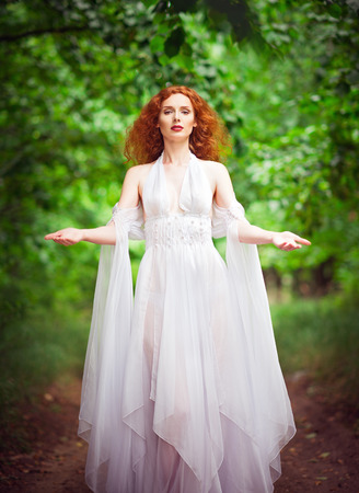 forest trees: Beautiful redhead woman wearing white dress in the forest Stock Photo