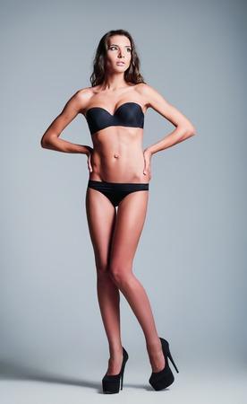 skinny woman: Studio fashion shot: a beautiful young girl wearing black lingerie and shoes Stock Photo