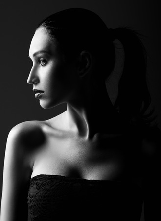 Studio shot: dramatic portrait of a beautiful young woman. Profile view. Black and white Stock Photo