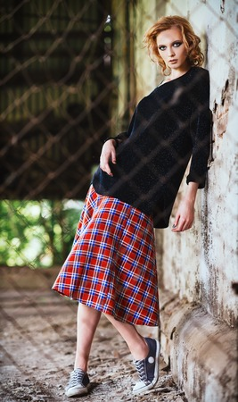 checkered skirt: Grunge fashion: beautiful young girl in checkered skirt and blouse stands behind the lattice