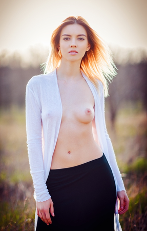 girls naked: Portrait of a sexy young woman with open chest in the field at sunset