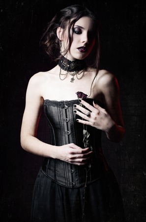 goth girl: Dramatic portrait of beautiful sad goth girl holding a withered rose in hands. Grunge texture effect