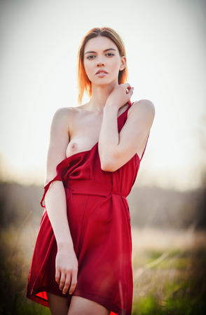 breasts pretty: Portrait of a sexy young woman wearing red dress in the field at sunset. Topless