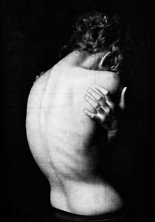 Spooky portrait of a young woman among the dark. Grunge texture effect. Black and white, rear view