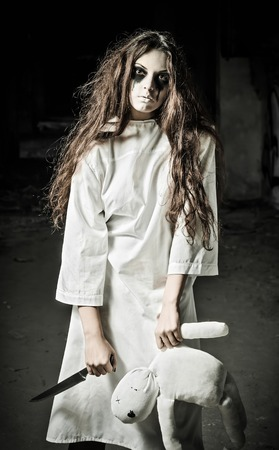 Horror style shot: a strange sad girl with moppet doll and knife in hands 스톡 콘텐츠
