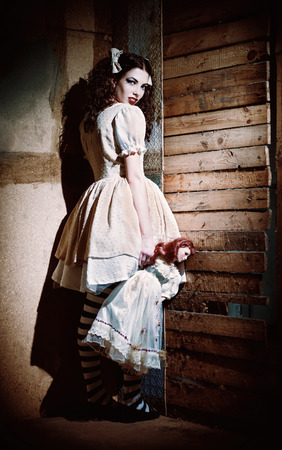 madhouse: Portrait of a weird scary girl with doll in hand